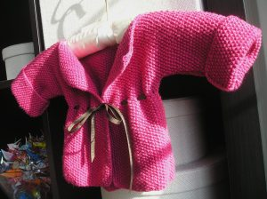"""Baby Cardigan"" finished, with ribbon, and photographed at a rakish angle"